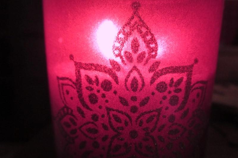 Pinke Kerze mit Ornamenten.